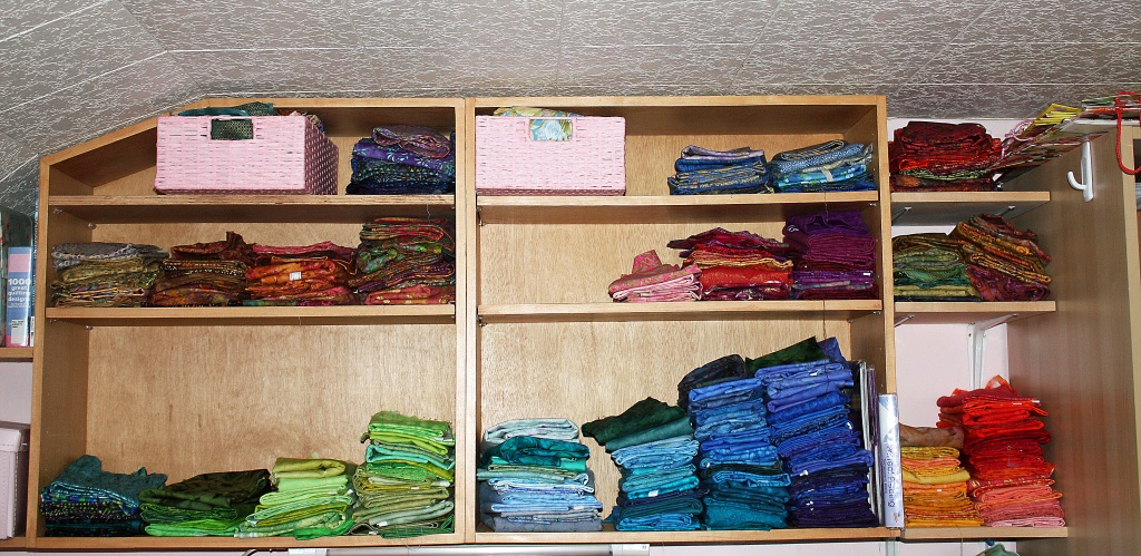One of the 3 shelves holding fabric. This one is being organised, a loty of fabric waiting to go home.