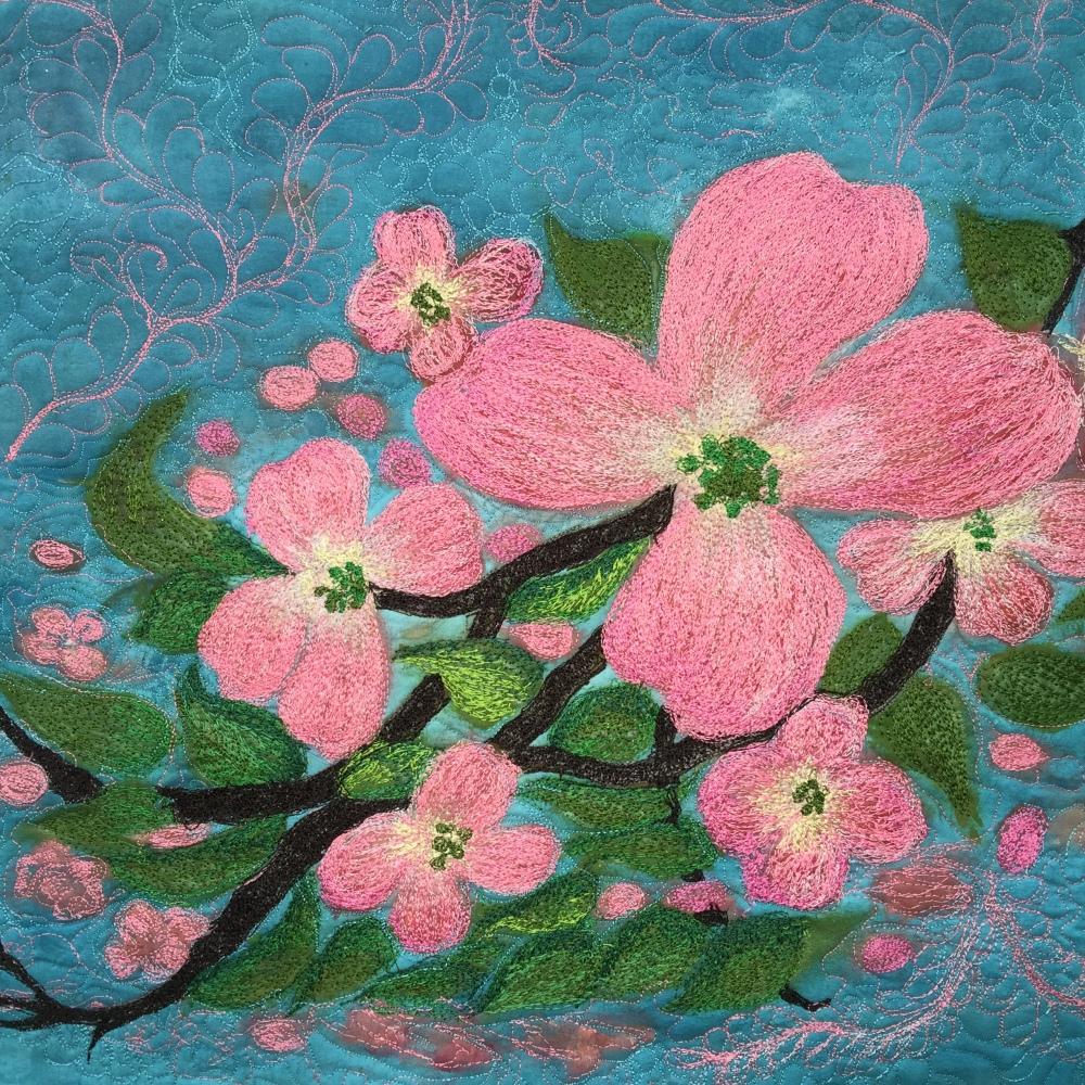 A silk painted fiber art quilt, blue skys and pink dogwoods
